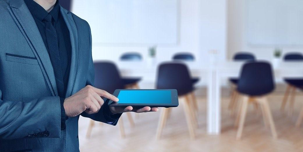 Homem de terno e tablet em mãos com uma sala de reunião ao fundo
